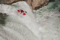 Vista di alto angolo di maschio kayaker in montagna cascata fluisce il fiume Elk superiore, Fernie, Columbia britannica, Canada — Foto stock