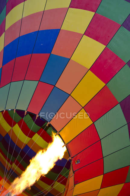 Ballooning burner flame heating hot air balloon, full frame. - foto de stock