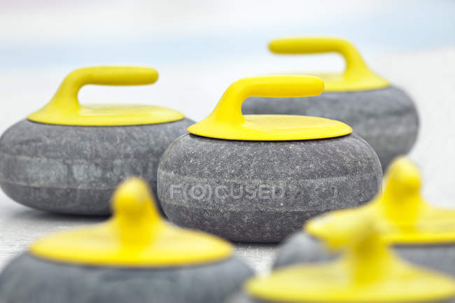 Close-up of yellow curling stones on ice. — Stock Photo