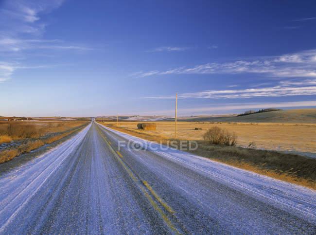 Grand Valley road through prairie near Cochrane in winter, Alberta, Canadá . — Fotografia de Stock