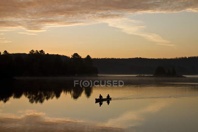 Dois homens remar de canoa ao nascer do sol no lago Oxtongue, Muskoka, Ontário, Canadá. — Fotografia de Stock
