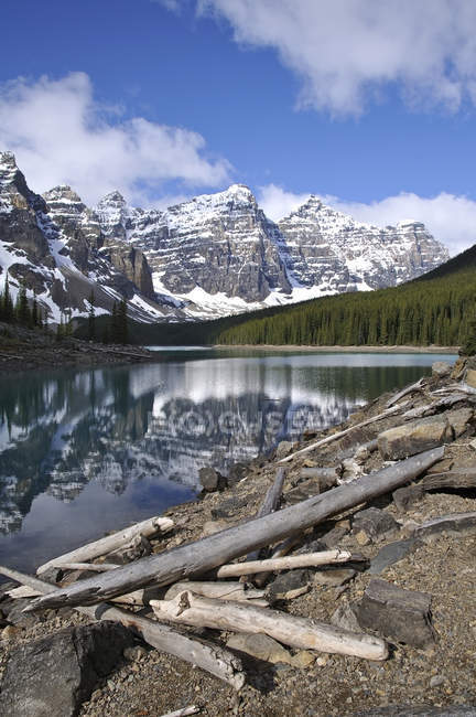 Rocky shore of Moraine Lake with logs and mountain reflection in Banff National Park, Alberta, Canada — Stock Photo