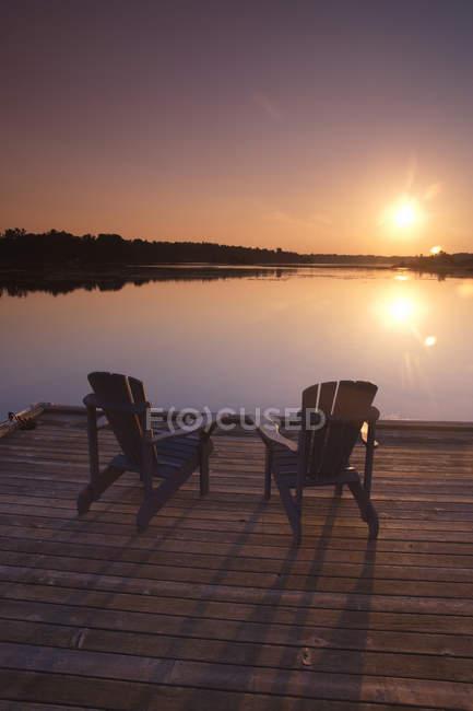 Chaises Adirondack sur une jetée en bois au lever du soleil sur le lac Sparrow, Muskoka, Ontario — Photo de stock