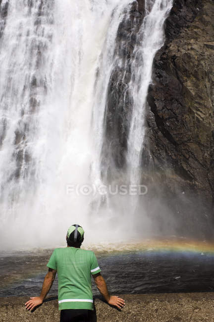 Cyclist watching flowing Montmorency Falls, Quebec City, Quebec, Canada. — Stock Photo