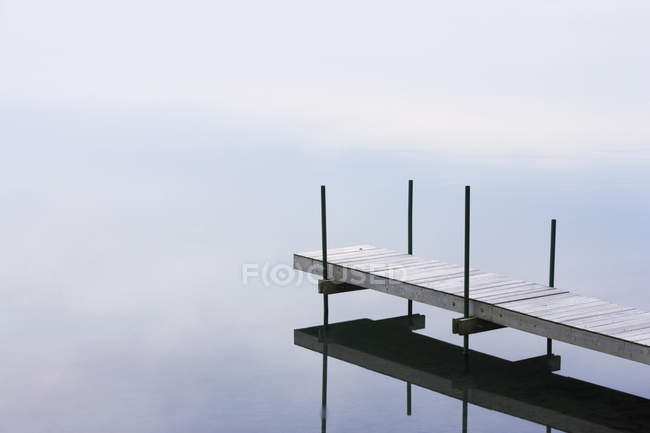 Wooden dock along river water with reflection. — Stock Photo
