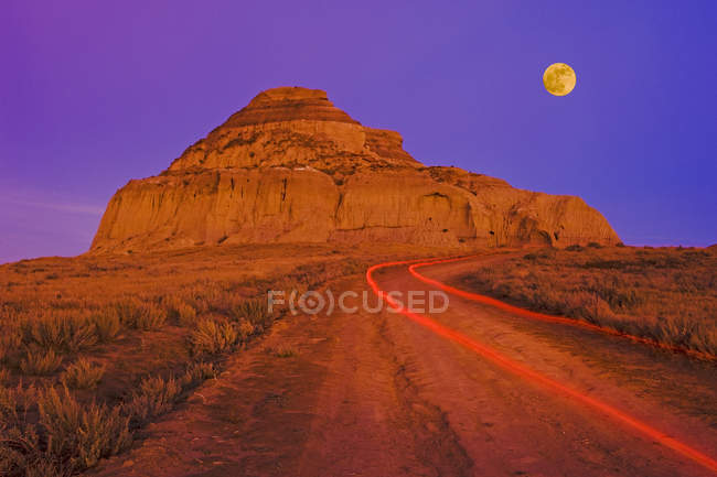Tail lights on road with Castle Butte rock in Big Muddy Badlands, Saskatchewan, Canada — Stock Photo