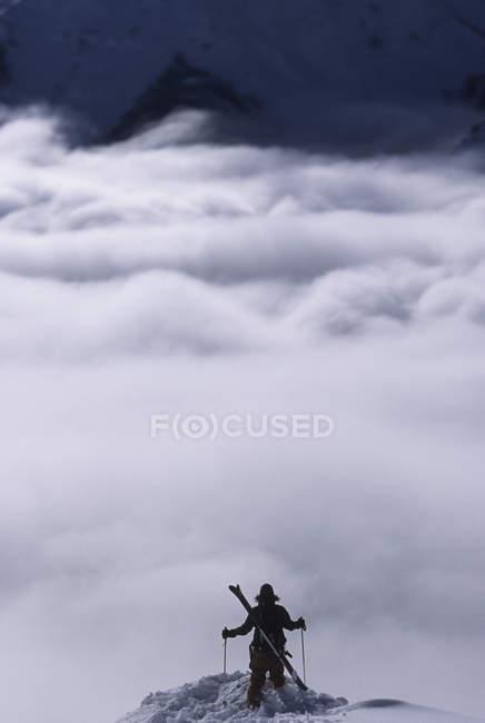 Person admiring mountains clouds at Kicking Horse Resort, Golden, British Columbia, Canada. — Stock Photo