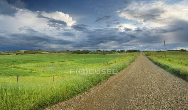 Country road with field and fence with storm clouds near Cochrane, Alberta, Canada — Stock Photo