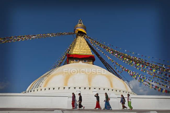 Menschen, die vorbeigehen Boudhanath Stupa mit Gebetsfahnen an geistigen Standort in Kathmandu, Nepal. — Stockfoto