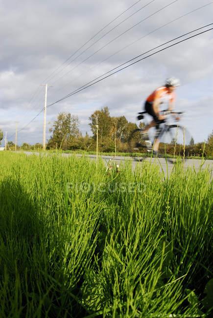 Ireconhecível pessoa estrada ciclismo em Finn Slough, Richmond, British Columbia, Canadá — Fotografia de Stock