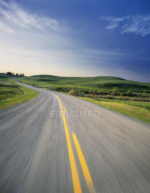 Road through pastureland near Cochrane, Alberta, Canada. — Stock Photo