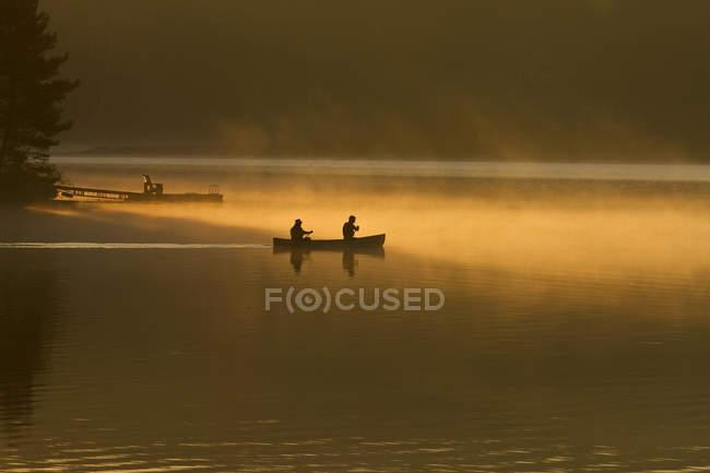 Deux hommes pagaie canoë au lever du soleil sur Oxtongue Lake, Muskoka, Ontario, Canada. — Photo de stock