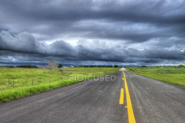 Estrada do país e nuvens de tempestade perto de Cochrane, Alberta, Canadá — Fotografia de Stock