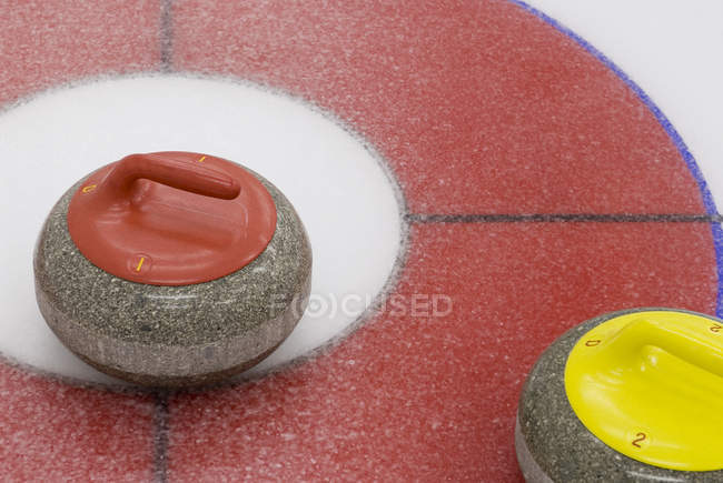 Close-up of red and yellow curling stones on ice. — Stock Photo