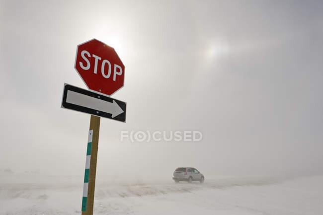 Deje de firmar y montar en coche en la carretera cubierto de nieve soplando cerca de Morris, Manitoba, Canadá - foto de stock