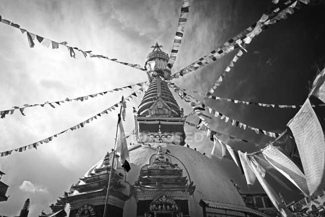 Low angle view of Kathe Simbu Stupa and flags in center of Kathmandu, Nepal — Stock Photo
