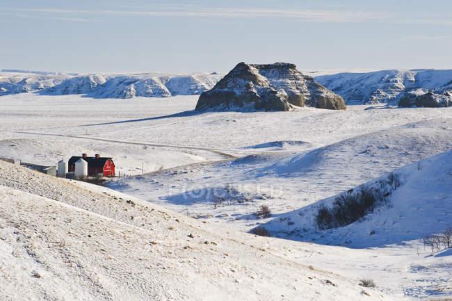 Große schlammige badlands mit burg butte hill und roter scheune in saskatchewan, kanada — Stockfoto
