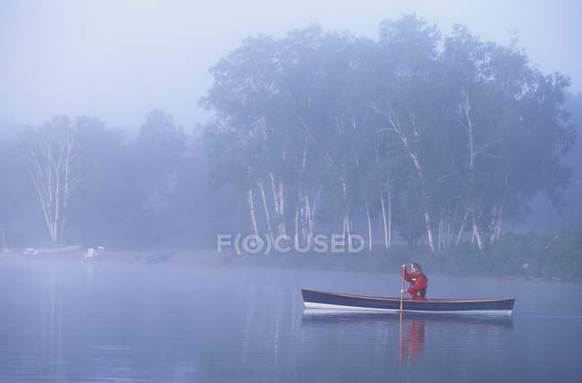 Young woman canoeing in early morning mist, Oxtongue Lake, Muskoka, Ontario, Canada. — Stock Photo