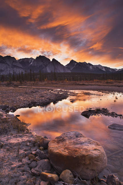 Dramatic sky over rocky shore of North Saskatewan River along Kootenay Plains of Alberta, Canada. — Stock Photo