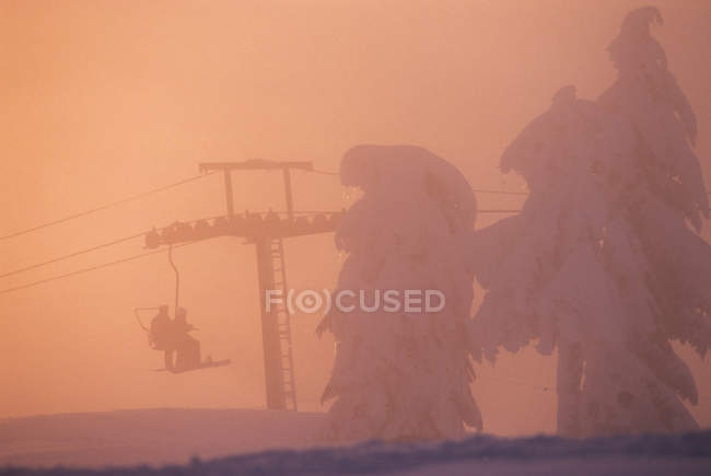 Silhouettes of people riding chair lift at Cypress Mountain Resort, British Columbia, Canada. — Stock Photo