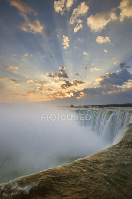 Cataratas de herradura bajo cielo nublado con rayos brillantes de luz solar, Cataratas del Niágara, Ontario, Canadá . - foto de stock