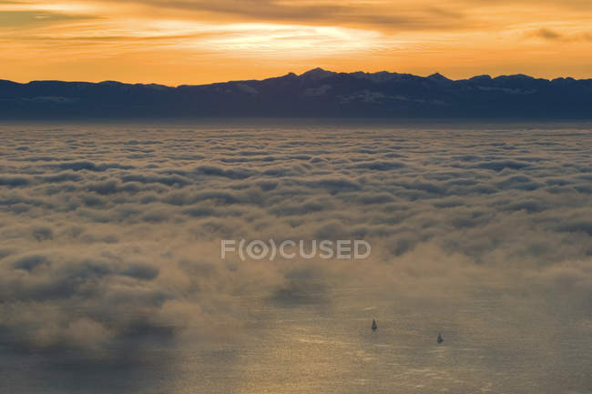 Sailboats appearing in ocean covered with fog and clouds with sun setting behing mountains, British Columbia, Canada. — Stock Photo