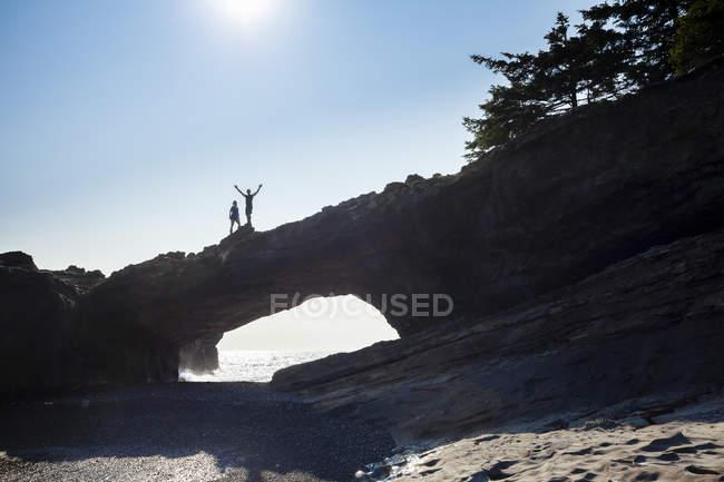 Два туристи, що стоять на вершині морської арки на Tsussea Point, Західне узбережжя стежка, Тихоокеанський Національний парк заповідник, острів Ванкувер, Канада. — стокове фото