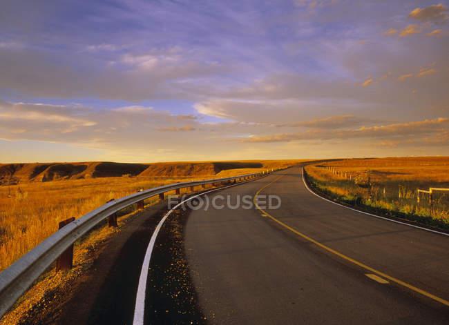 Salida del sol por carretera en Horsethief Canyon cerca de Drumheller, Alberta, Canadá . - foto de stock