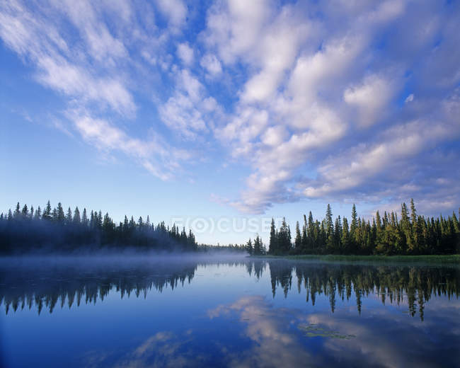Trees reflection in blue water of Grass River, Northern Manitoba, Canada — Stock Photo
