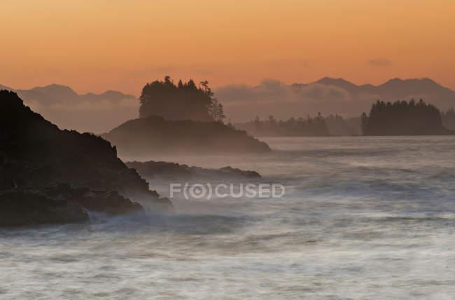 Sunrise over rocks in sea near Ucluelet, Vancouver Island, British Columbia, Canada — Stock Photo
