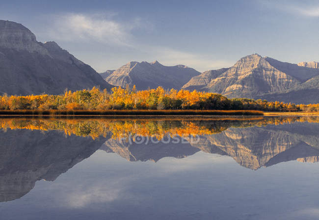Autumnal woodland reflecting in Maskinonge Lake, Waterton Lakes National Park, Alberta, Canada. — Stock Photo
