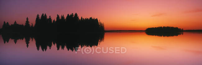 Mirrored reflection in Astotin Lake at sunset in Elk Island National Park, Alberta, Canada. — Stock Photo