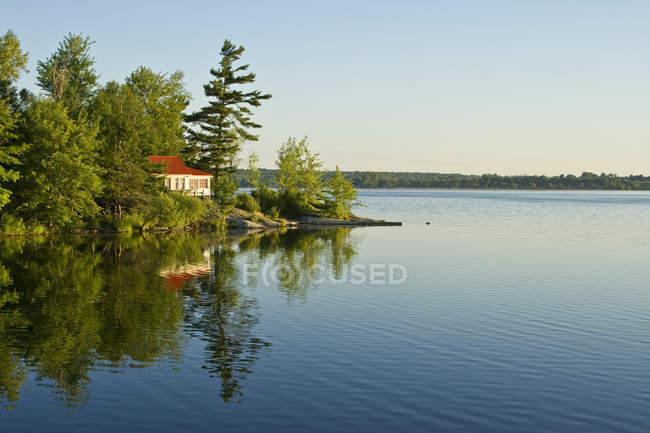 Cottage avec vue sur un lac calme au nord de Kingston, Ontario, Canada — Photo de stock