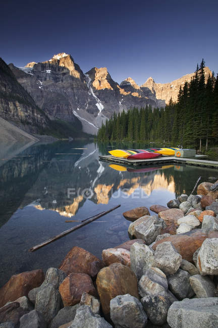 Rocky coast of Moraine Lake with canoes, Banff National Park, Alberta, Canada — Stock Photo