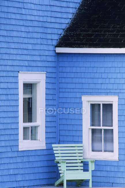 Exterior of blue house with white windows and green wooden chair — Stock Photo