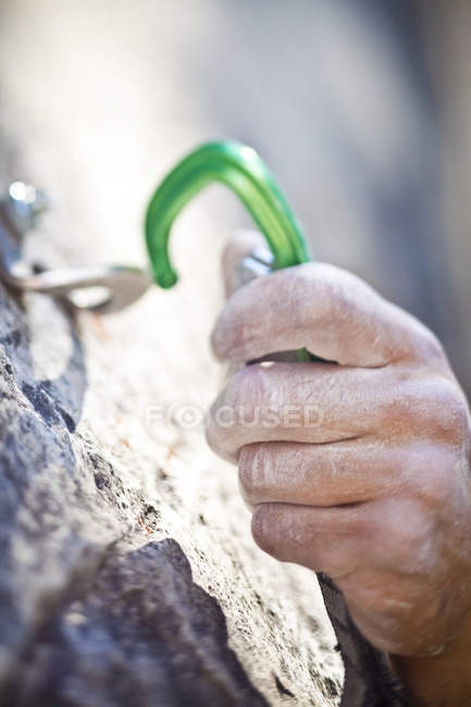 Hand of man sport climbing on rock face in sunlight — Stock Photo