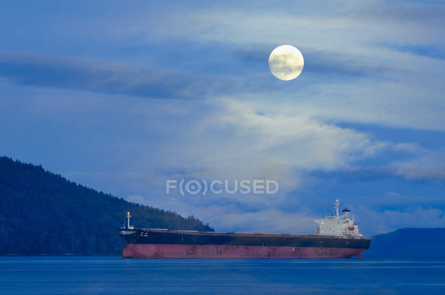 Freighter ship under full moon in Satellite Channel near Vancouver Island, British Columbia, Canada. — Stock Photo