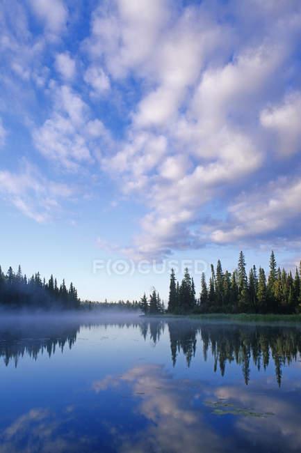 Nuages reflétant dans l'eau de la rivière Grass, nord du Manitoba, Canada — Photo de stock