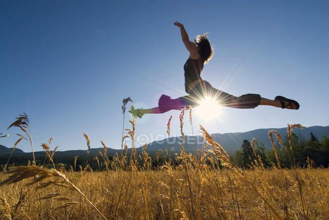 Bailarina saltando en el campo de hierba con el sol brillando, Tatlayoko Lake, British Columbia, Canadá. - foto de stock