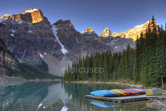 Frostige Kanus, die bei Sonnenaufgang am Moränensee im Tal der zehn Gipfel festmachen, Banff-Nationalpark, Alberta, Kanada. — Stockfoto
