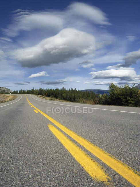 Highway under clouds in blue sky at Bighorn Wildland, Alberta, Canada — Stock Photo