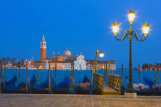 Gondolas with church of Saint George Major in distance at night, Venice, Italy — Stock Photo