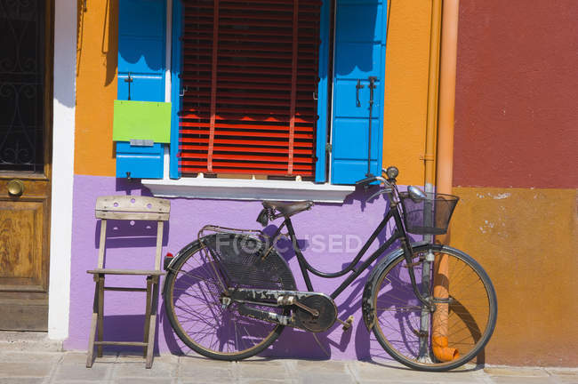 Old bicycle and chair leaning against colourfully painted wall, island of Burano, Venice, Italy — Stock Photo