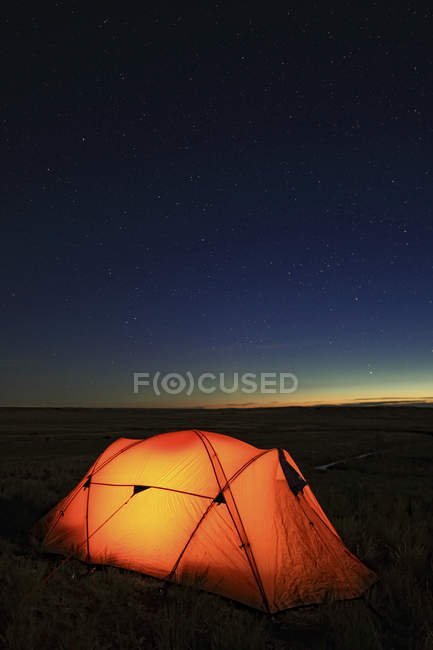 Tenda illuminata di notte, affacciata sulla valle del fiume di Frenchman, Grasslands National Park, Saskatchewan, Canada. — Foto stock