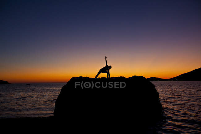 Silhouette of woman practicing yoga on coastal rock at sunrise in Kalymnos, Greece. — Stock Photo