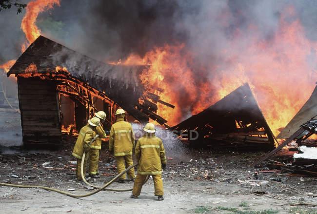 Пожарные обливание горящего здания, Британская Колумбия, Канада. — стоковое фото