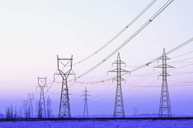 Torres de transmissão de energia ao entardecer perto de Winnipeg, Manitoba, Canadá . — Fotografia de Stock