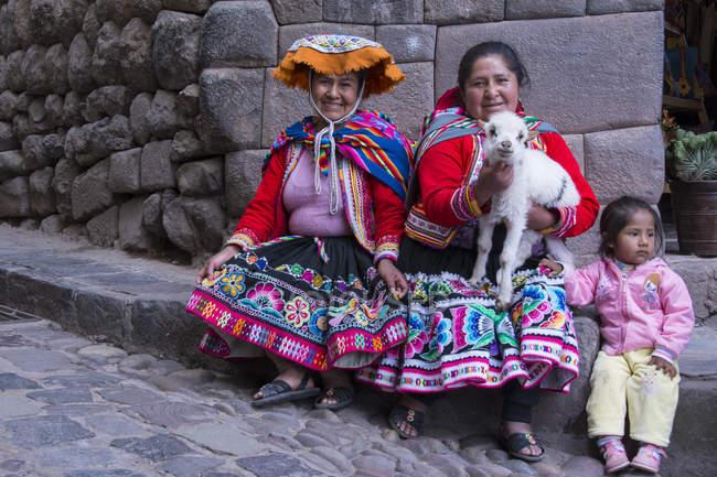 Місцевих жінок у традиційному одязі з дитиною і баранина на вулицю села місті Pisac, Перу — стокове фото