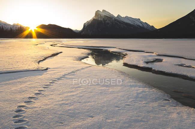 Alba accanto al Monte Rundle riflettendo sul ghiaccio sul lago Vermilion innevato in inverno nel Banff National Park, Alberta, Canada . — Foto stock