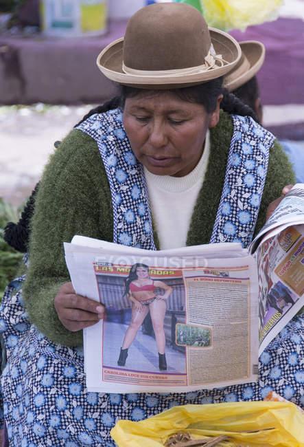 Mujer leyendo el periódico en la escena del mercado de Puno, Lago Titicaca, Perú - foto de stock